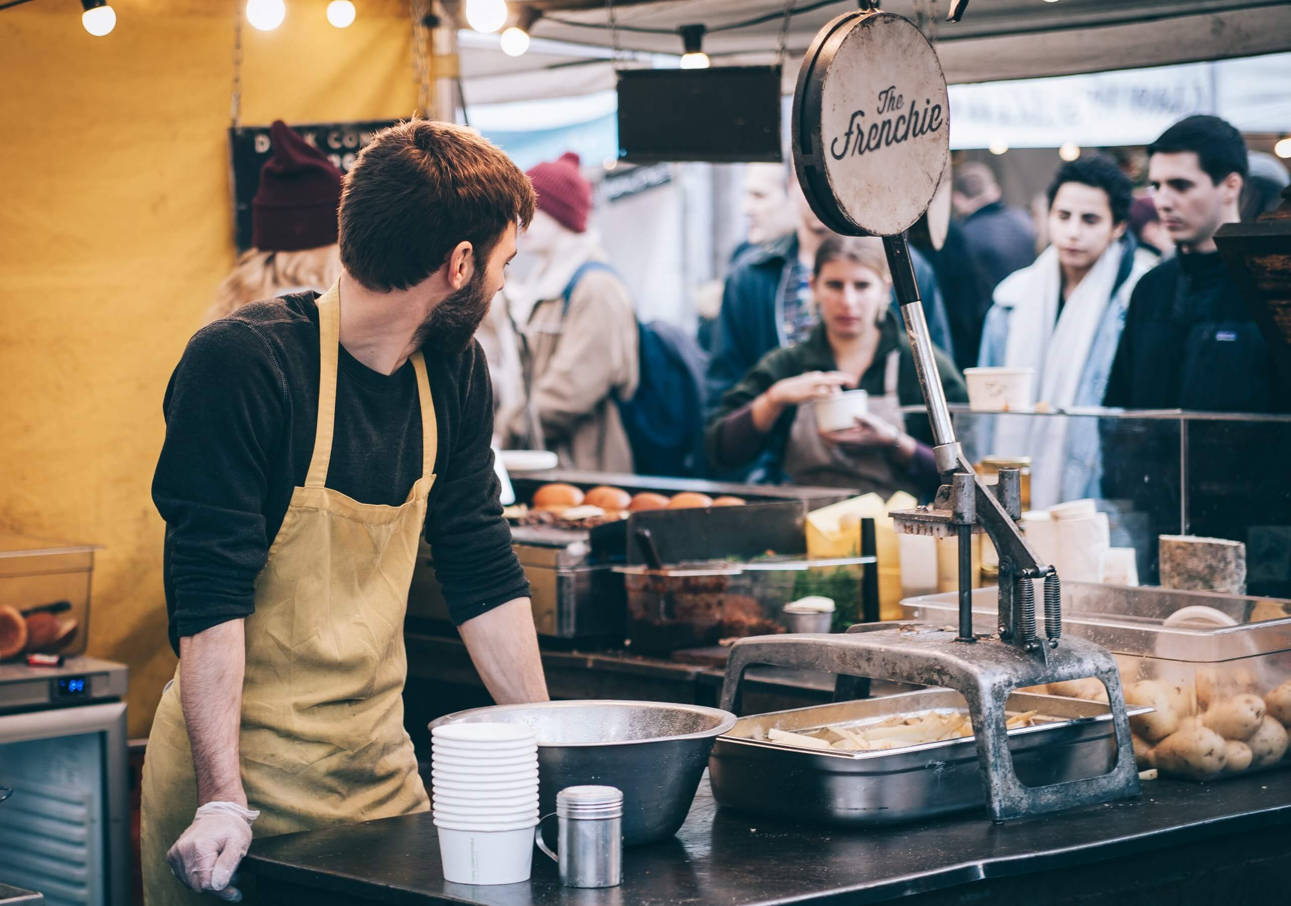 man serving at a food stall